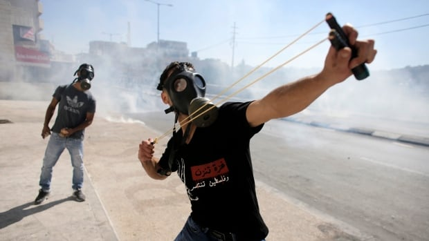 A Palestinian protester uses a slingshot to throw a stone at Israeli troops during clashes at a protest against the Israeli offensive in Gaza, in the West Bank town of Bethlehem. The writing on the T-shirt reads 'Gaza is bleeding and Palestine is winning.'