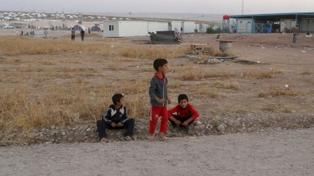 Displaced Iraqi boys from the Yazidi community wait at the entrance of a camp at Feeshkhabour town in Iraq near the border with Syria on Saturday. They were separated from family members during their escape from fighting in Northern Iraq.