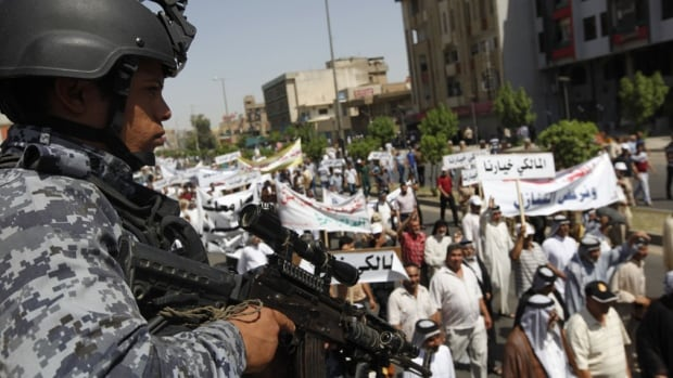 An Iraqi police officer stands guard during a demonstration in support of Iraqi Prime Minister Nuri al-Maliki in Baghdad on Saturday.  August 9, 2014. Pro-Maliki supporters took to the streets of Baghdad on Saturday to support al-Maliki's bid for a third term in office.