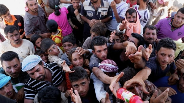 Displaced Iraqis from the Yazidi community gather earlier this week for humanitarian aid at the Iraq-Syria border at Feeshkhabour border point. The United States is considering a plan to rescue Yazidis and others threatened by Islamic militants in Iraq.