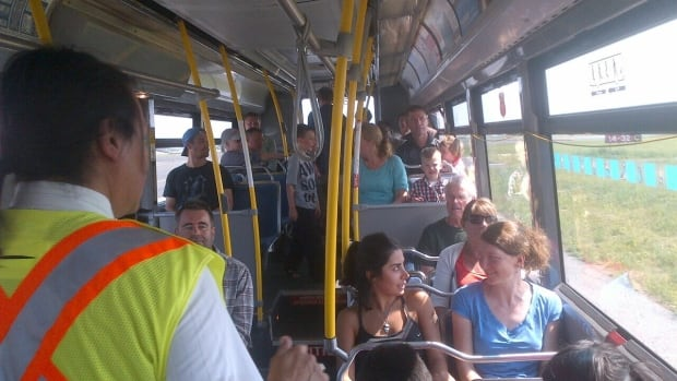 Passengers take a bus back to the terminal after being de-planed from a Canadian North flight.