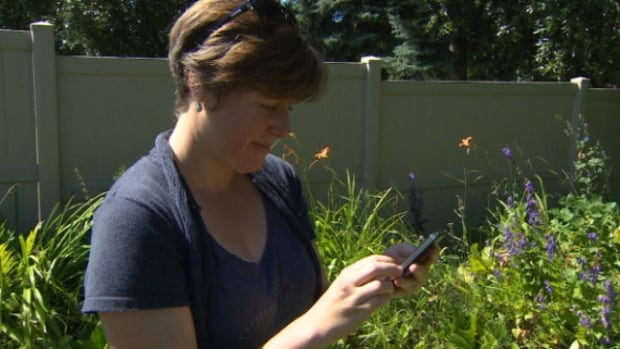 Lesley Harrington uses the new Alberta Weed Spotter app to check some plants in her garden.