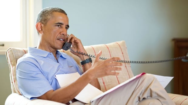 U.S. President Barack Obama is seen, in this photo released by the White House, talking on the phone with Prime Minister Stephen Harper from his vacation retreat at Martha's Vineyard, Mass., on Aug. 12, 2014. The two leaders discussed the situation in Iraq amid a worsening humanitarian crisis.