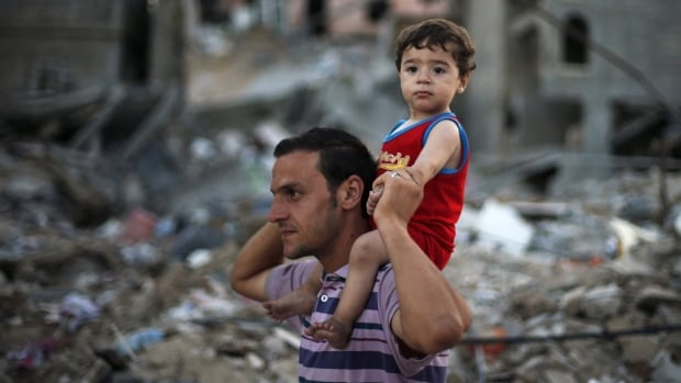 A Palestinian holds his son as they walk past houses, which witnesses said were destroyed in an Israeli offensive, during a 72-hour truce in Beit Hanoun town in the northern Gaza Strip Aug. 12, 2014.
