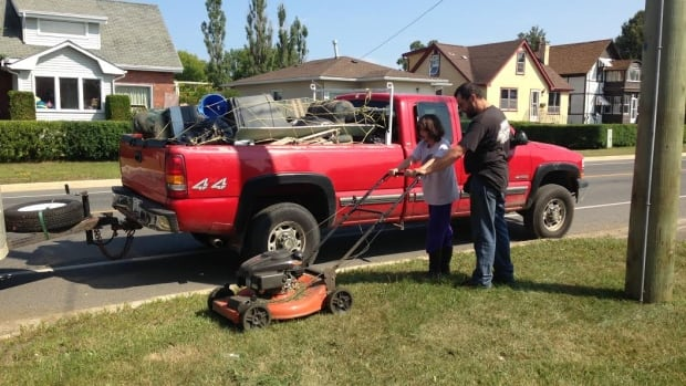 Geoff Sutton shows his 10-year-old daughter Naomi how to use a lawnmower.