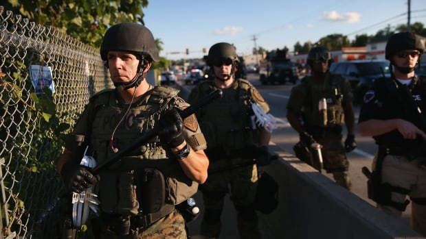 Police in combat gear take up position to control demonstrators who were protesting the killing of teenager Michael Brown on Aug. 12. Images like these have sparked a review of programs channelling weapons from the Pentagon to local police departments.