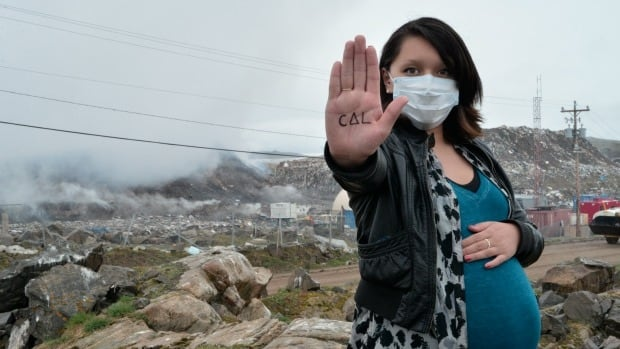 "Julie Alivaktuk at the Iqaluit dump in early July. ""Taima"" or ""enough"" is written on her hand in syllabics. The citizens group Iqalummiut for Action, is hoping that the military will lend a hand to put the fire out when personnel are in town for Operation Nanook."