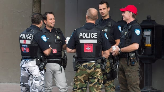 Montreal Police officers are shown on a street in Montreal, Thursday, August 7, 2014. The funky pants and sticker-plastered city vehicles are just the beginning as workers and the province draw battle lines over a proposed reform of municipal pensions.