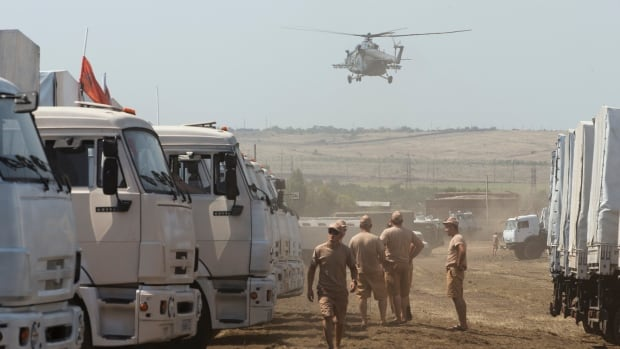 A Russian military helicopter prepares to land near a convoy of white trucks with humanitarian aid parked in a field about 28 kilometers from Ukrainian border in Rostov-on-Don region, Russia.