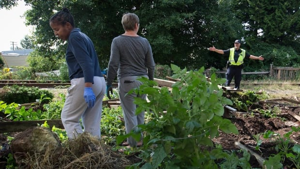 A Canadian Pacific Rail police officer, right, directs residents Sarah Myambo, left, and Mila Rakhmetouline off the property for their safety as they try to salvage items from their community garden.