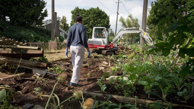 Resident Sarah Myambo watches as workers remove her community garden from a stretch of abandoned CP Rail line in Vancouver, B.C., on Thursday August 14, 2014.