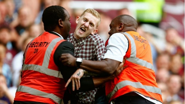 Stewards restrain a pitch invader during the match between Tottenham and West Ham United match.