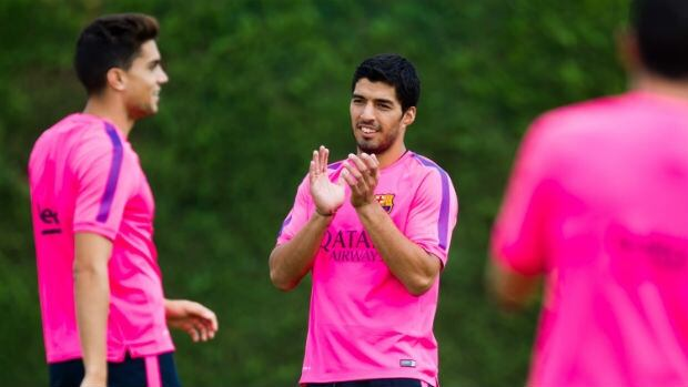 Luis Suarez, centre, claps during a Barcelona training session.