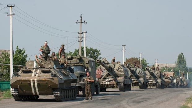A Ukrainian army column of military vehicles rolls to the eastern region where Ukrainian officials say pro-Russian rebels were fighting a desperate rearguard action to hold on to Luhansk.