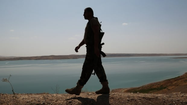 A Kurdish Peshmerga fighter patrols near the Mosul Dam, less than two weeks after it was captured by the ISIS extremist group.