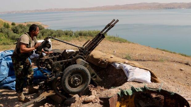 Kurdish forces, known as peshmerga, stand guard near the Mosul Dam in Iraq Sunday.