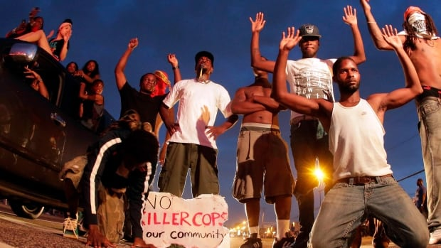 A group of young protesters pose on Aug. 17 with their hands in the air, a pose now associated with Michael Brown's fatal shooting by a police officer. Photos like this circulated on social media with people across the country imitating the gesture in solidarity with Ferguson.