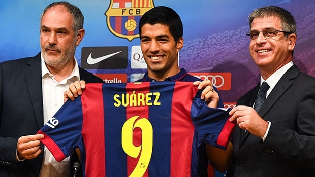 Luis Suarez, centre, poses with FC Barcelona executives Andoni Zubizarreta, left, and Jordi Mestre at Tuesday's news conference.