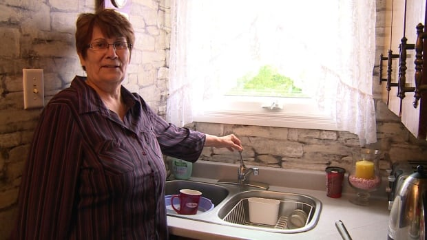 Birchy Brook resident Margaret Bennett stands next to her tap, which yields no water.