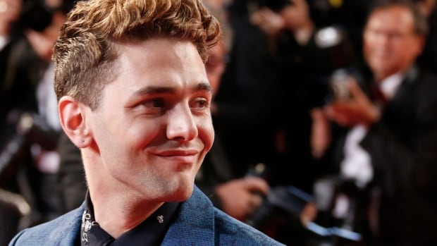 Director Xavier Dolan poses on the red carpet as he arrives for the screening of the his new film, which went on to win a prestigious Cannes Film Festival prize.