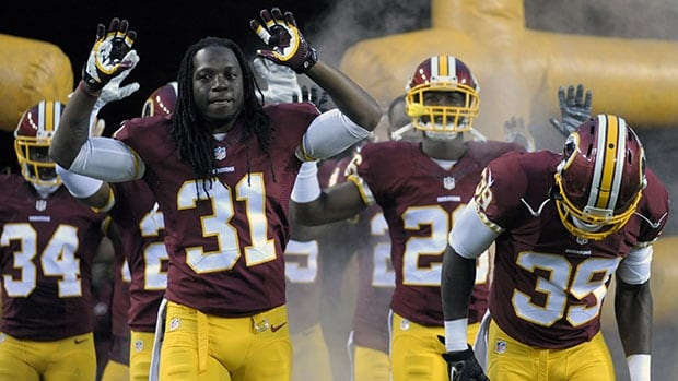 Washington players, led by strong safety Brandon Meriweather (31), take the field with their arms raised before an NFL exhibition game.