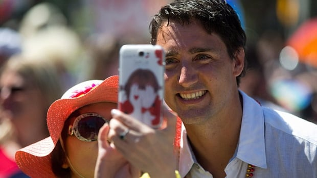 A woman uses her phone to take a photo of herself with Liberal leader Justin Trudeau during the Vancouver Pride Parade in Vancouver, B.C., on Sunday August 3, 2014.