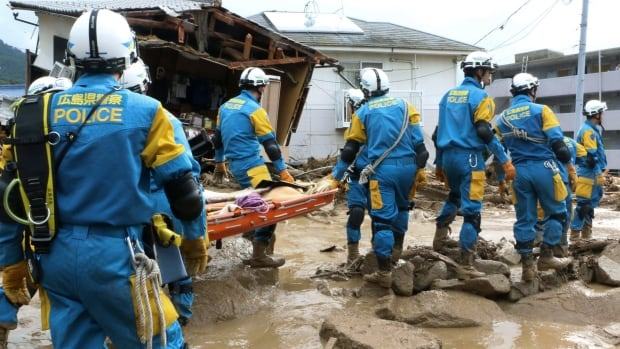 A troop of police rescue personnel head out for rescue operation after a massive landslides swept through residential area in Hiroshima, western Japan on Wednesday.
