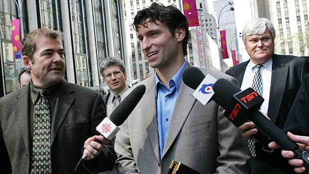 Steve Moore, middle, talks to CBC Sports reporter Tom Harrington, left, outside NHL headquarters in New York on April 26, 2005.
