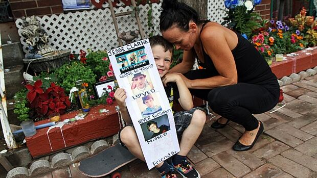 Melissa Mercuri and her son, Andre, sit at the makeshift memorial outside the home of Jesse Clarke's parents in the east end of Hamilton. Clarke, 14, was stabbed Monday night on Gordon Street, just north of Barton.