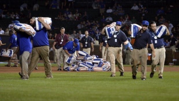 Grounds crew carry bags of diamond dry on the field following a rain delay during the fifth inning of the Chicago Cubs-San Francisco Giants game at Wrigley Field on Tuesday.