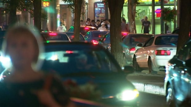 Whyte Avenue is jammed with vehicles and pedestrians on a typical weekend night.