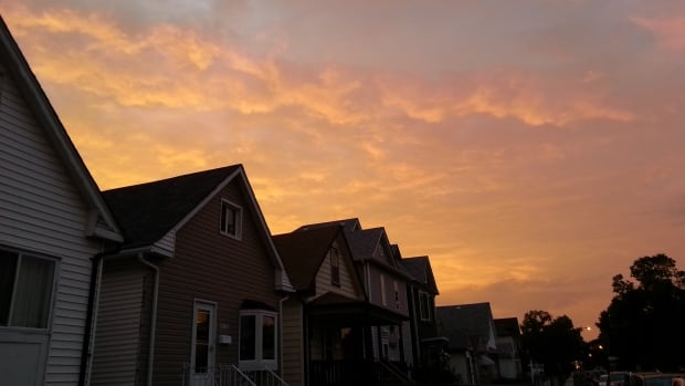 Overcast and a yellow-orange sunrise over homes in Winnipeg's West end Thursday morning.