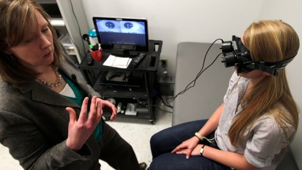 Physical therapist Anne Mucha, left, explains a test she is demonstrating on high school soccer player Madison MacDonald who suffered a concussion on the pitch.  Concussions are not always the result of bruising brawls or body blows, a hockey coach says.
