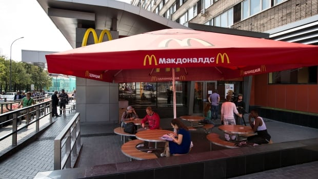 People walk past the oldest McDonald's outlet in Russia in downtown Moscow, which opened in 1990 and was one of four branches shut down this week by the country's food safety agency.