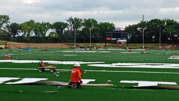 Crews install new turf at Saskatoon Minor Football Field at Gordie Howe Park.