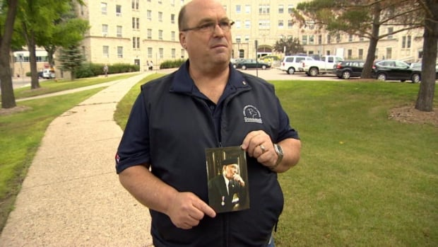 Tom Armstrong, with a photo of his 95-year-old father Roy. The elderly man was referred by doctors to long term care, but an assessment found he did not meet the criteria for that level of care.