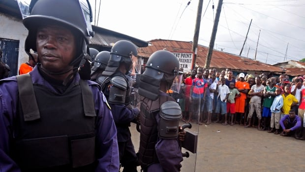 Liberia security forces dressed in riot gear, left, control a crowd of people in the West Point area, as the government clamps down on the movement of people to prevent the spread of the Ebola virus in Monrovia