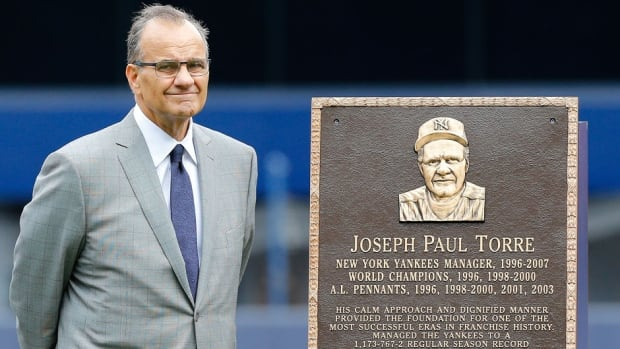 Former Yankees manager Joe Torre stands with his plaque that was installed in Monument Park at Yankee Stadium during a ceremony prior to Saturday's game against the Chicago White Sox.