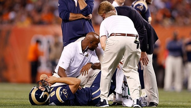 Rams quarterback Sam Bradford (8) is treated onfield by trainers at FirstEnergy Stadium in Cleveland, Ohio, on Saturday night.