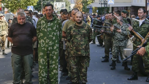 Armed pro-Russian separatists escort a column of Ukrainian prisoners of war as they walk across central Donetsk, a rebel-held town in eastern Ukraine, on Sunday in a show of defiance to Ukrainian authorities who were celebrating the 23rd anniversary of the country's independence from the Soviet Union.