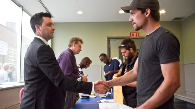 A recruiter, left, shakes hands with a job seeker at National Steel Car's job fair on Saturday. About 1,100 people turned out for the event that aimed to fill 400 positions at the plant.