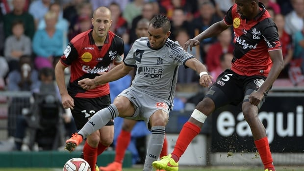 Marseille's forward Dimitri Payet, middle, tries to control the ball against Guingamp in French league action on Saturday. During the match, Payet raised eyebrows with a corner  kick that hit the scoreboard.
