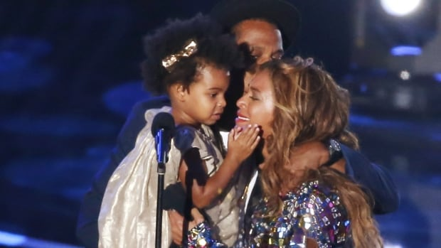 Beyoncé kisses her daughter Blue Ivy at the MTV VMAs Sunday. BET has suspended a producer for a joke suggesting the 2-year-old's parents don't brush her hair.
