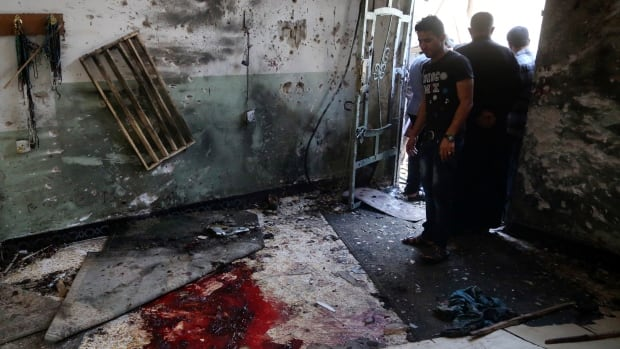 Worshippers look at blood stains inside the Imam Ali mosque after a suicide bomb attack in Baghdad Monday.
