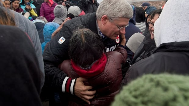 Prime Minister Stephen Harper hugs a woman as he is welcomed to Arctic Bay, Nunavut Monday August 25, 2014. A survey was circulated Tuesday to Conservative donors and 'grassroots supporters' to 'hear what issues matter to you the most.'
