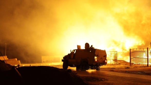 A building on fire, which witnesses say was hit by a rocket, burns after clashes between rival militias in the Sarraj district in Tripoli on Aug. 23.