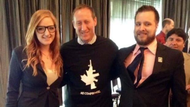 Justice Minister Peter MacKay, centre, wears a pro-gun T-shirt as he poses with Erica Clarke, left, and Kurtis Gaucher at a Conservative Party fundraising event in Edmonton. Clarke, who works for the National Firearms Association, posted the photo to her Facebook page.
