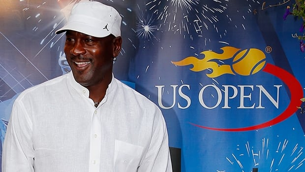 Michael Jordan poses briefly for photographers upon his arrival at the U.S. Open in Flushing Meadows, N.Y., on Tuesday night.