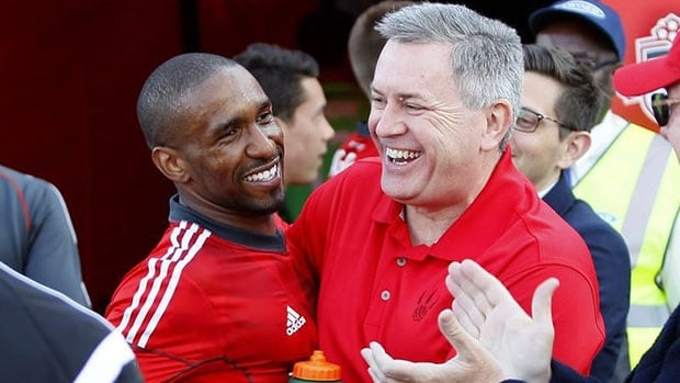 Outgoing MLSE CEO and president Tim Leiweke, right, seen here greeting TFC striker Jermain Defoe in May, says his desire to be an entrepreneur led to his impeding resignation.