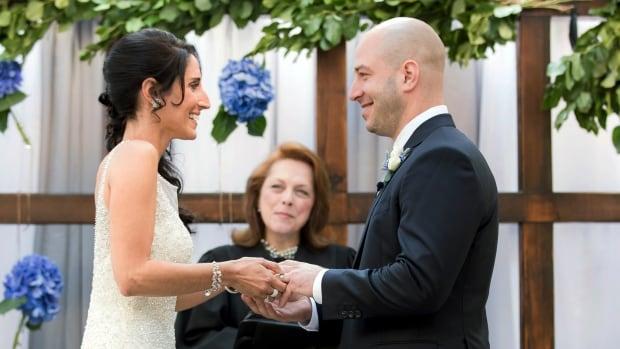 In this photo taken on Saturday, Aug. 23, 2014, and released by Hyatt Regency Boston, Boston Marathon bombing survivor, James Costello, right, marries Krista D'Agostino.
